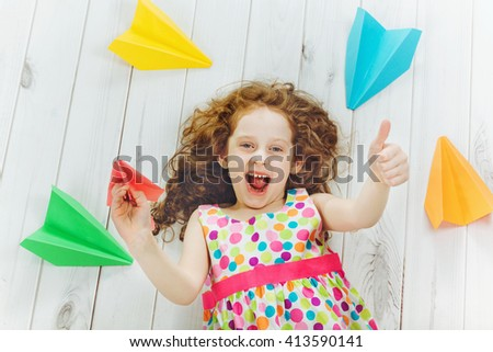 Laughing girl throwing paper airplane indoors and , showing thumbs up.