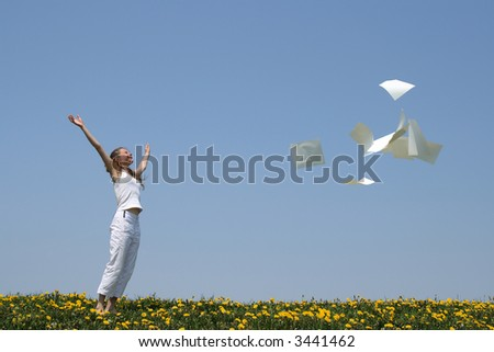 Laughing girl throws in air blank paper sheets (with copy space), freeing herself from paperwork. - stock photo