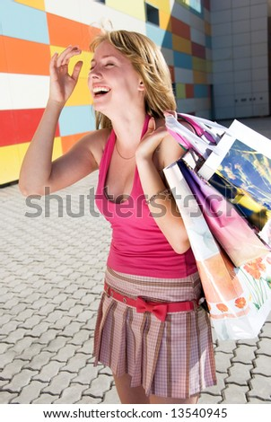 Laughing girl with bags after shopping