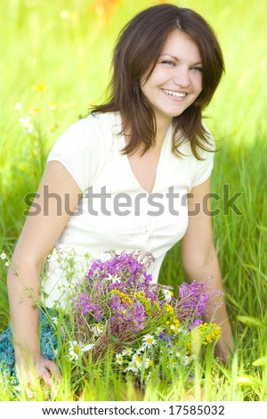 laughing girl with bunch on grass - stock photo