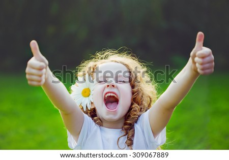 Laughing girl with daisy in her hairs, showing thumbs up. - stock photo