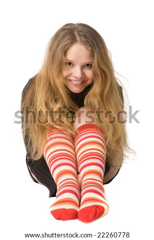 laughing girl with long hair in long brown sweater and red-orange long socks sitting on the floor, isolated on white
