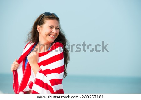 laughing girl with red striped towel on the beach - stock photo