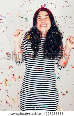 Laughing girl with striped dress and wool cap under a rain of confetti. Filter effect added. Some blur in arms because of the movement. - stock photo