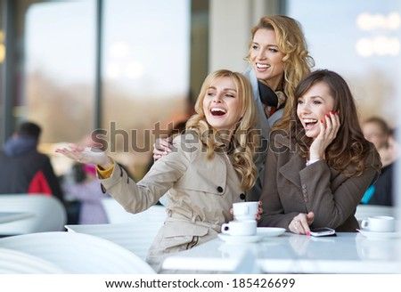 Laughing girlfriends in the cofee shop - stock photo