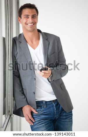 Laughing Gorgeous young man leaning on a glass wall and texting