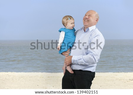 laughing grandfather with granddaughter, outdoors at the beach