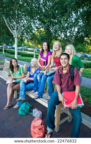 Laughing group of five high school girls and one boy sitting on a bench holding books. Vertically framed photo. - stock photo