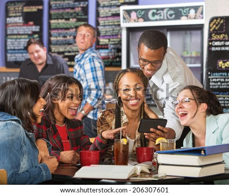 Laughing group of students looking at cell phone - stock photo