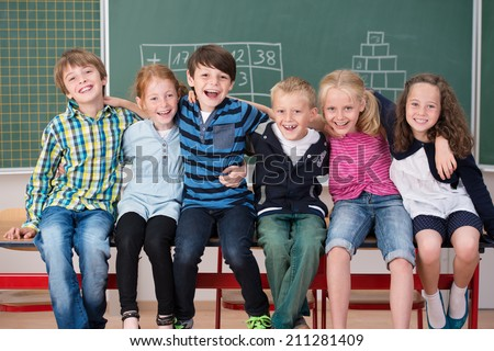 Laughing group of young friends in class sitting in a row in front of the chalkboard grinning happily at the camera - stock photo