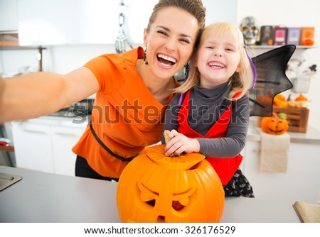 Laughing halloween dressed girl and young mother making selfie with big orange pumpkin Jack-O-Lantern in decorated kitchen. Traditional autumn holiday - stock photo