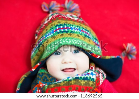 Laughing happy baby in a colorful knitted hat and scarf - stock photo