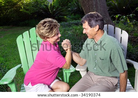 Laughing, happy couple arm wrestling in a green outdoor setting