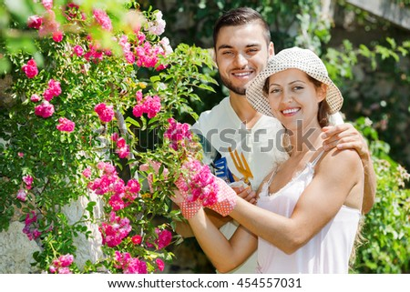 Laughing happy couple working in the flower garden