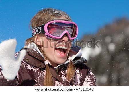Laughing happy girl on winter sport vacation. Wearing ski mask