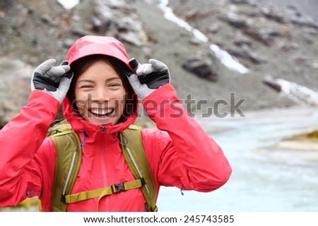 Laughing happy woman hiking with backpack in rain on trek living healthy active lifestyle. Smiling cheerful girl walking on hike in beautiful mountain nature landscape raining, Swiss alps, Switzerland - stock photo