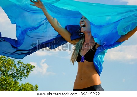 Laughing happy woman with arms up outdoors with blue cloth floating in air above her. Wearing a bikini top - stock photo