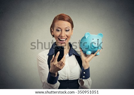 Laughing happy young woman holding piggy bank looking at smart phone isolated on gray background. Financial savings banking concept, customer satisfaction contract agreement. Positive face expression - stock photo