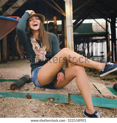 Laughing hipster girl portrait under the old pier on a sea beach, dressed in jeans shorts, skinny legs, autumn outdoor.