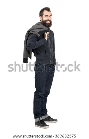 Laughing hipster with smiley piercing in upper lip holding jacket over the shoulder. Full body length portrait isolated over white studio background.