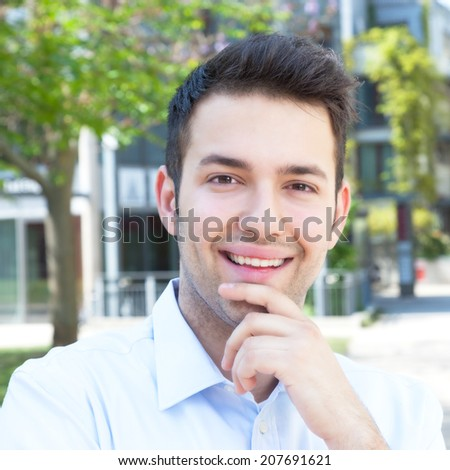 Laughing hispanic guy in a blue shirt  - stock photo