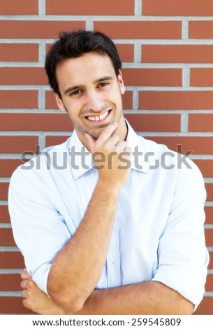 Laughing hispanic guy in front of a brick wall - stock photo