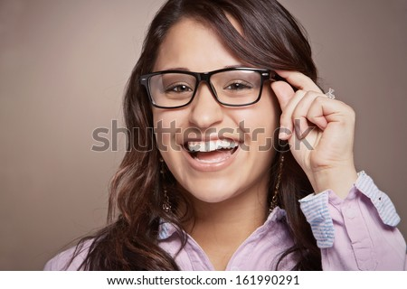 Laughing hispanic or latina pretty young woman with glasses