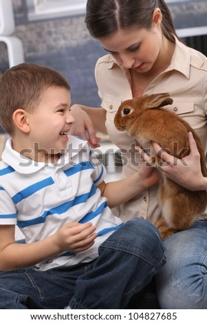 Laughing kid and young mom playing with pet rabbit at home.