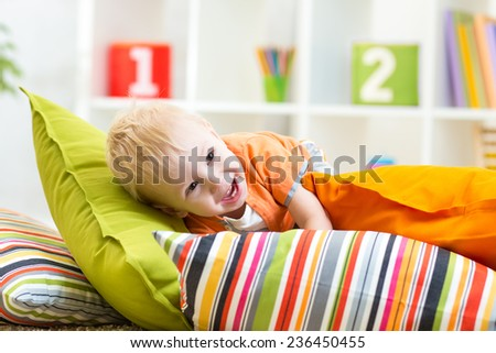 laughing kid boy playing on pillows in bedroom - stock photo