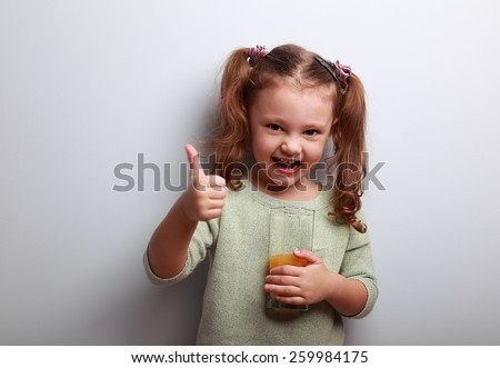 Laughing kid girl drinking juice and showing thumbs up sign on blue background - stock photo