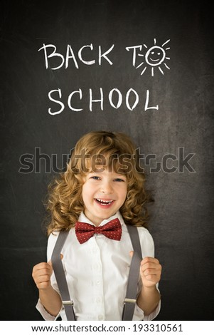 Laughing kid in class. Happy child against blackboard. Education concept - stock photo