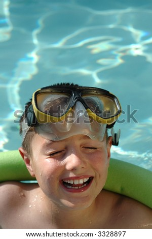 Laughing kid in the pool; plenty of copy space included - stock photo