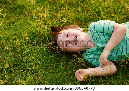Laughing kid lying on green grass in the park - stock photo