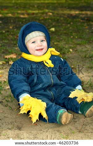 Laughing kid sits in an autumn park