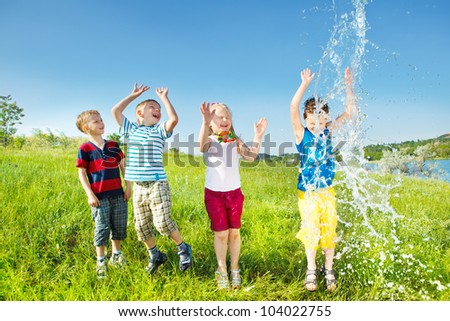 Laughing kids enjoying water splashes - stock photo