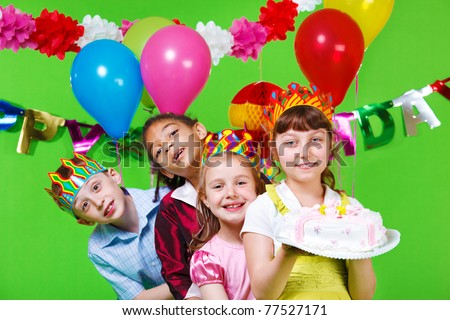 Laughing kids in party  hats and crowns holding birthday cake - stock photo