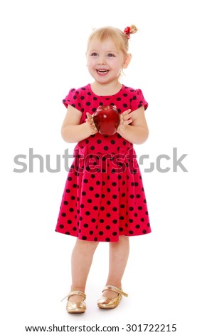 Laughing little blonde girl with a small pigtail at the head. The girl dressed in red polka dot dress and holding a front of a big red Apple.-Isolated on white background - stock photo