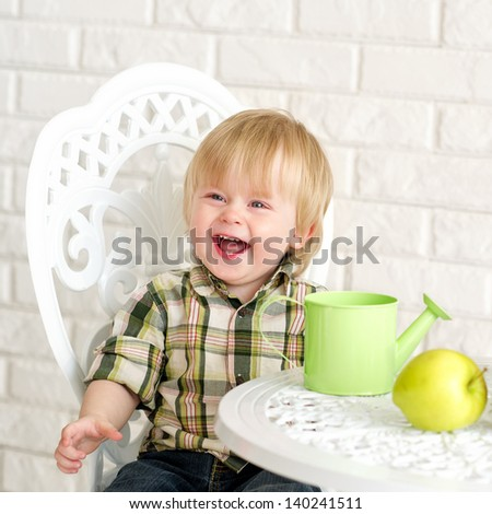 Laughing little boy at the table