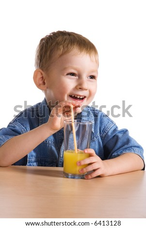 Laughing little boy drinking orange juice