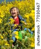 Laughing little boy drives toy car via rapeseed field in bloom - stock photo