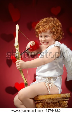 Laughing little boy in an image of the cupid does a shot - stock photo