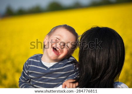 Laughing little boy in his mother's embrace. - stock photo