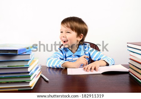 laughing little boy sitting at the desk. on the table are many books and a notebook. on a light background. horizontal