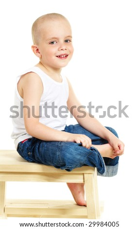 Laughing little boy sitting on stool