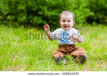 laughing little boy sitting on the grass