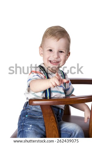 Laughing little boy sitting sideways on armchair and points his index finger at the camera isolated on white background - stock photo