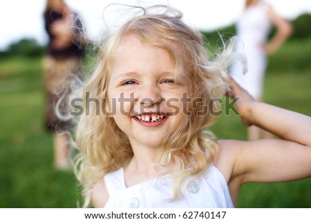 laughing little girl and two woman on background - stock photo
