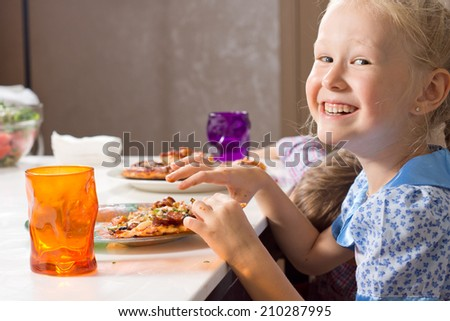 Laughing little girl eating homemade pizza at the table turning to look at the camera with a warm friendly smile