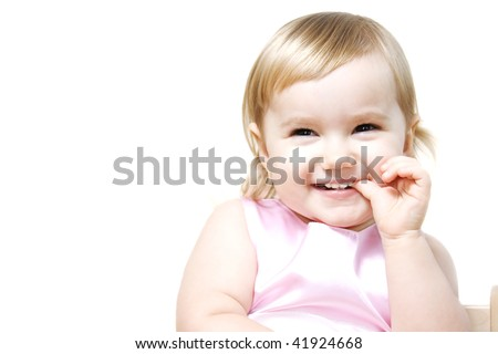 Laughing little girl holding finger in her mouth
