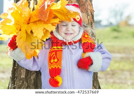 Laughing little girl holding yellow with orange autumn leaves bunch in hand outdoor portrait